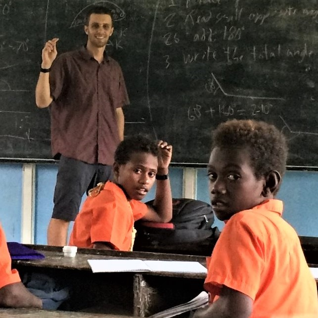 Undergraduate student Samuel Pilon standing at the blackboard in the front of a classroom, teaching math to young students in the Soloman Islands. The students are wearing bright orange shirts, three of whom are featured in the picture.