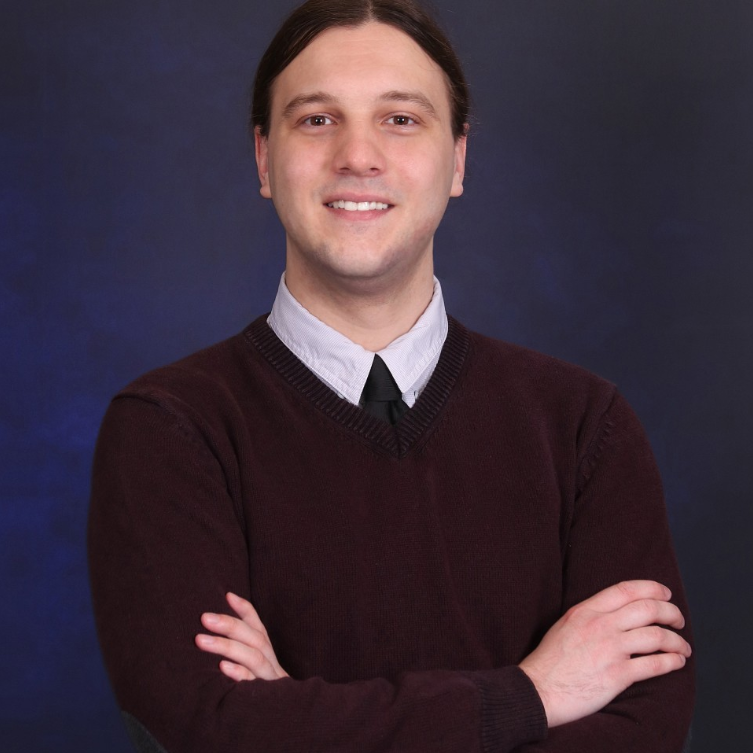 Graduate student Sébastien Lord is standing with his arms crossed and smiling. He is wearing a burgundy sweater. Behind him is a dark blue background.