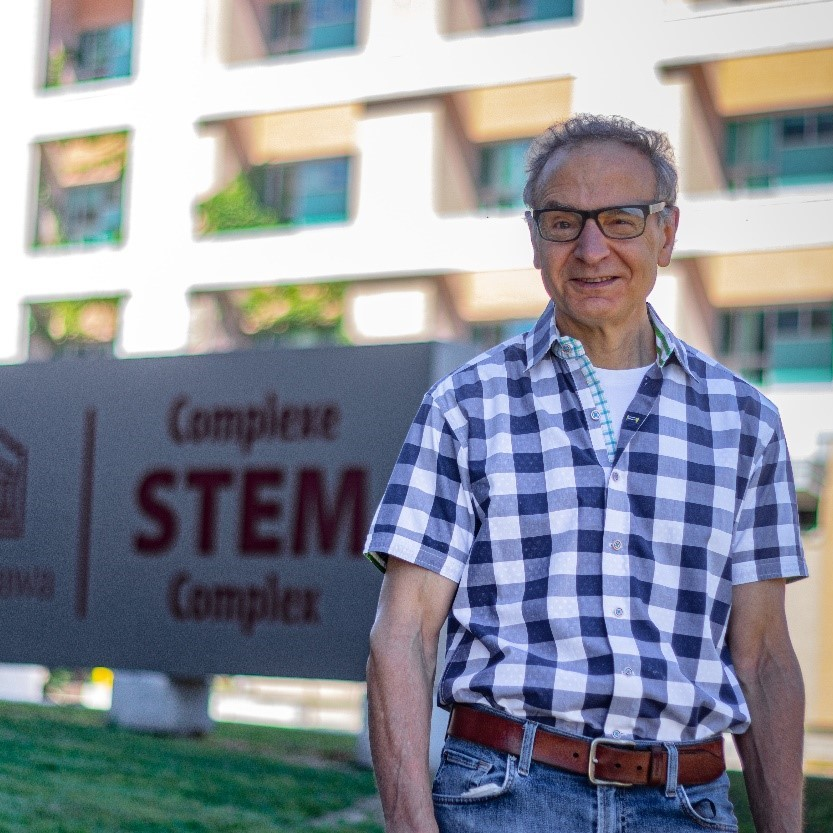 Professor Steve Perry stands on the grass in front of the sign for the STEM Complex on uOttawa Campus. We see the Biosciences Complex in the background.
