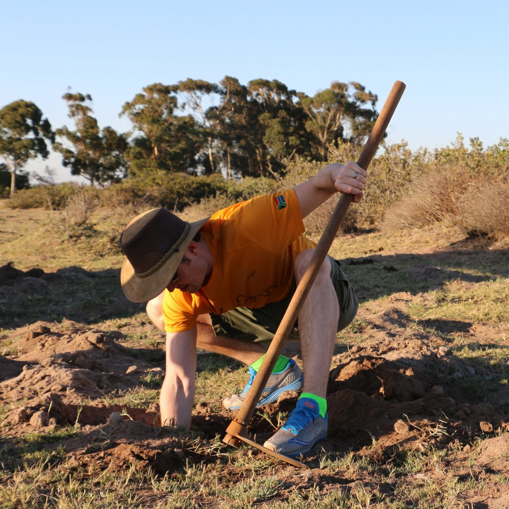 A man is crouched down in a field where the land has been turned. He holds a pickaxe in his left hand and inserts his right hand into a dirt hole