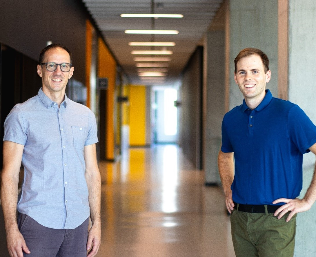(left to right) Professor Pascal Audet and PhD student Jeremy Gosselin stand a few feet apart, with a long corridor behind them.