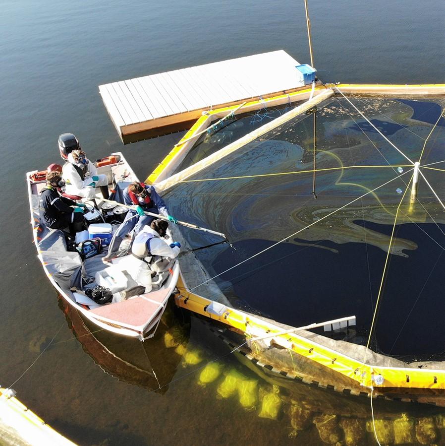 Quatre membres de l'équipe de recherche du Prof. Blais sont dans une petite embarcation qui se trouve sur un lac le long d'un limnocorrail