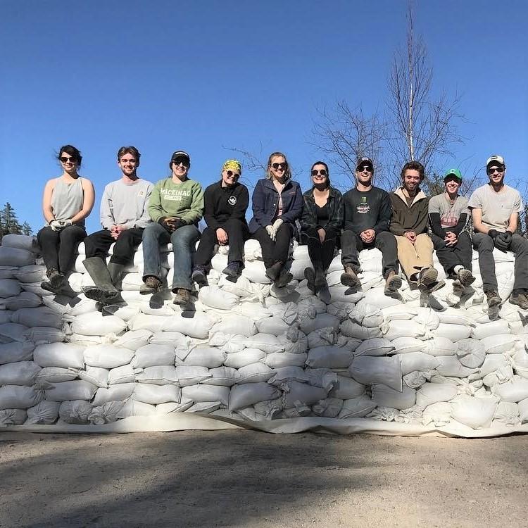 Des  étudiants gradués de la Faculté des sciences sont à l'extérieur, assis sur une montagne de sacs de sable. On voit des arbres derrière eux.