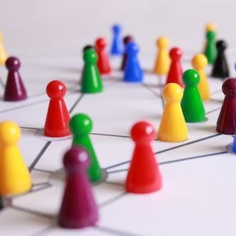 Pions multicolors interreliés sur une plaque de jeu.