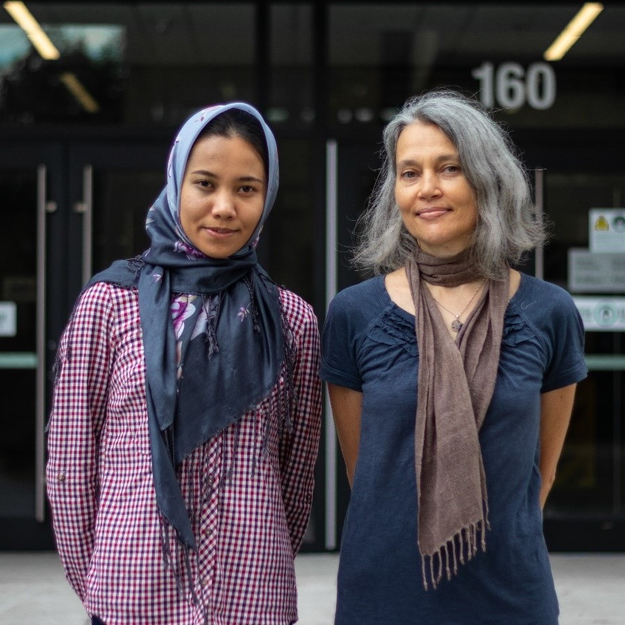 Professor Mateja Šajna (right) and MSc student Masoomeh Akbari (left) are standing side-by-side in front of the back entrance to the STEM Complex on uOttawa campus