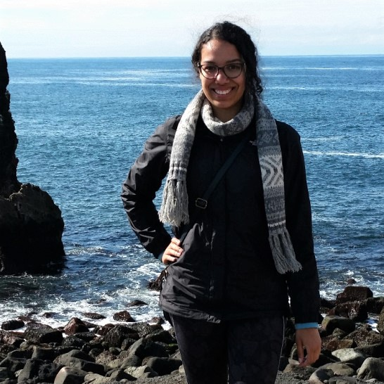 Undergraduate student Victoria Lee is standing outdoors, wearing a black jacket and a blue and white scarf. She is standing among rocks, with the ocean behind her.