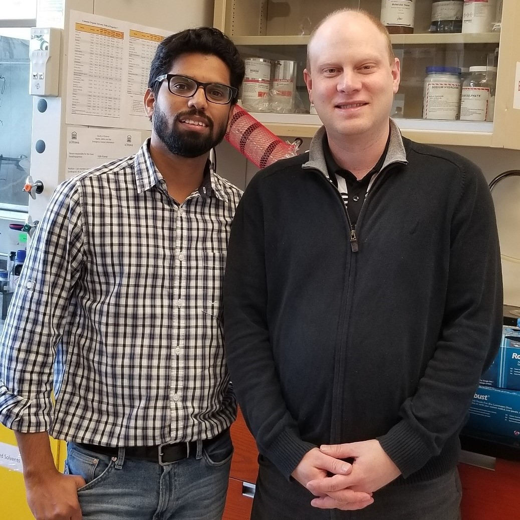 (left to right) Postdoctoral fellow Vijith Kumar and Professor David Bryce are standing in front of a laboratory bench. We see part of a fume hood and a cabinet holding chemicals behind them.