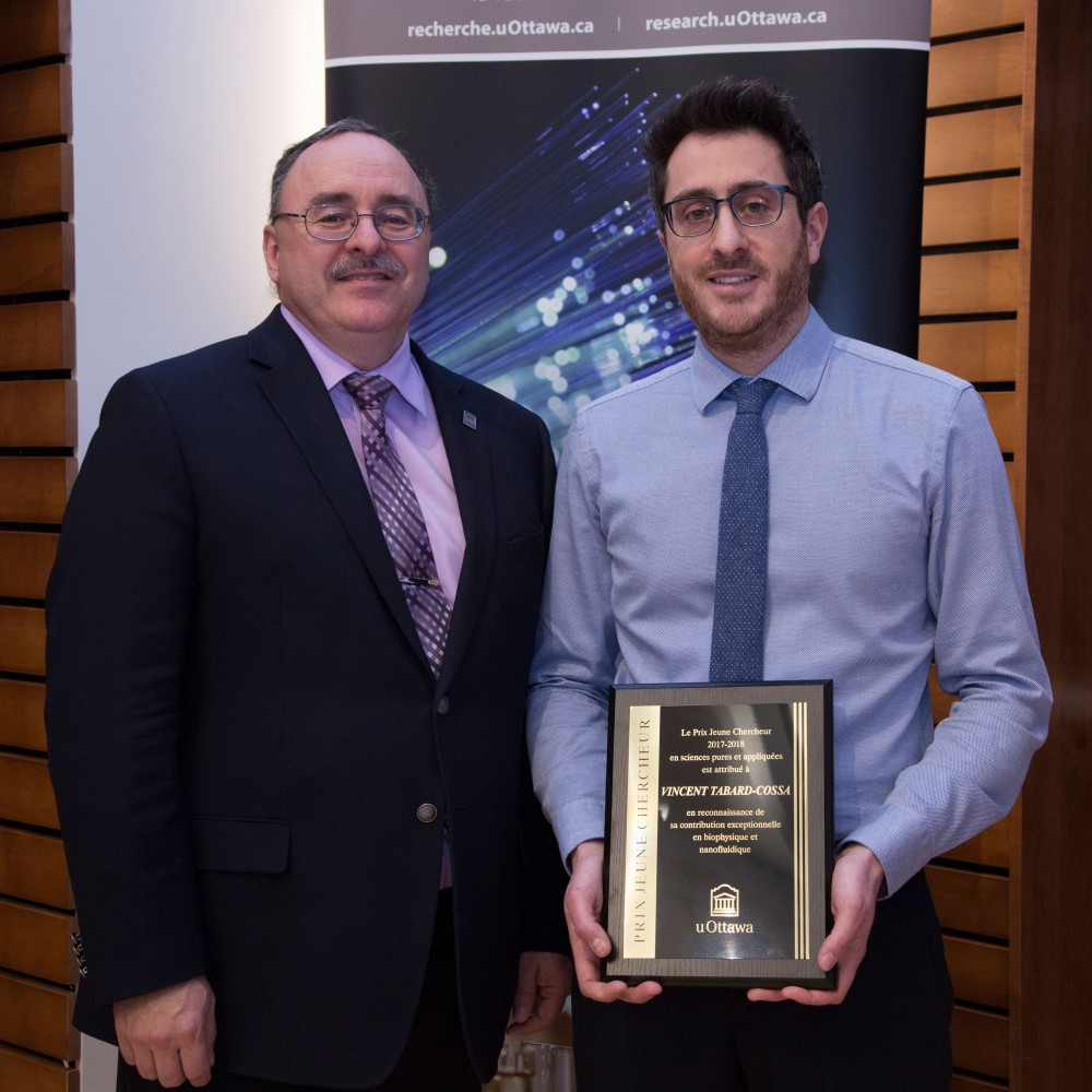 From left to right, Vice- President, Research, Sylvain Charbonneau is standing shoulder-to-shoulder beside Professor Vincent Tabard-Cossa, who is holding his newly received Young Researcher of the Year award plaque from the University of Ottawa.