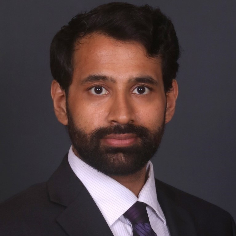 Omkar Zilka in front of a black background wearing a suit with a white shirt and a purple tie