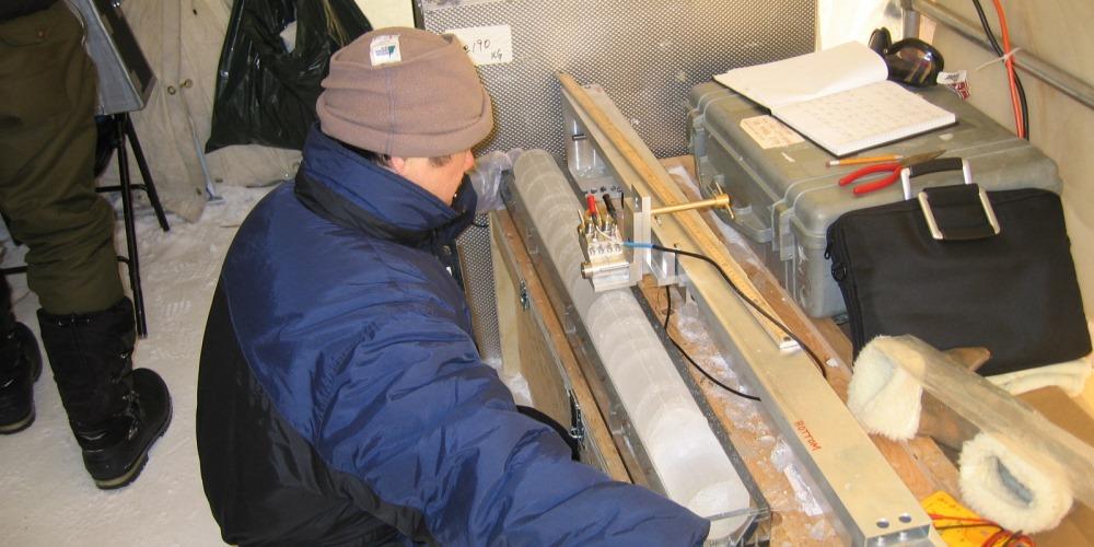 un scientifique mesure une carotte de glace