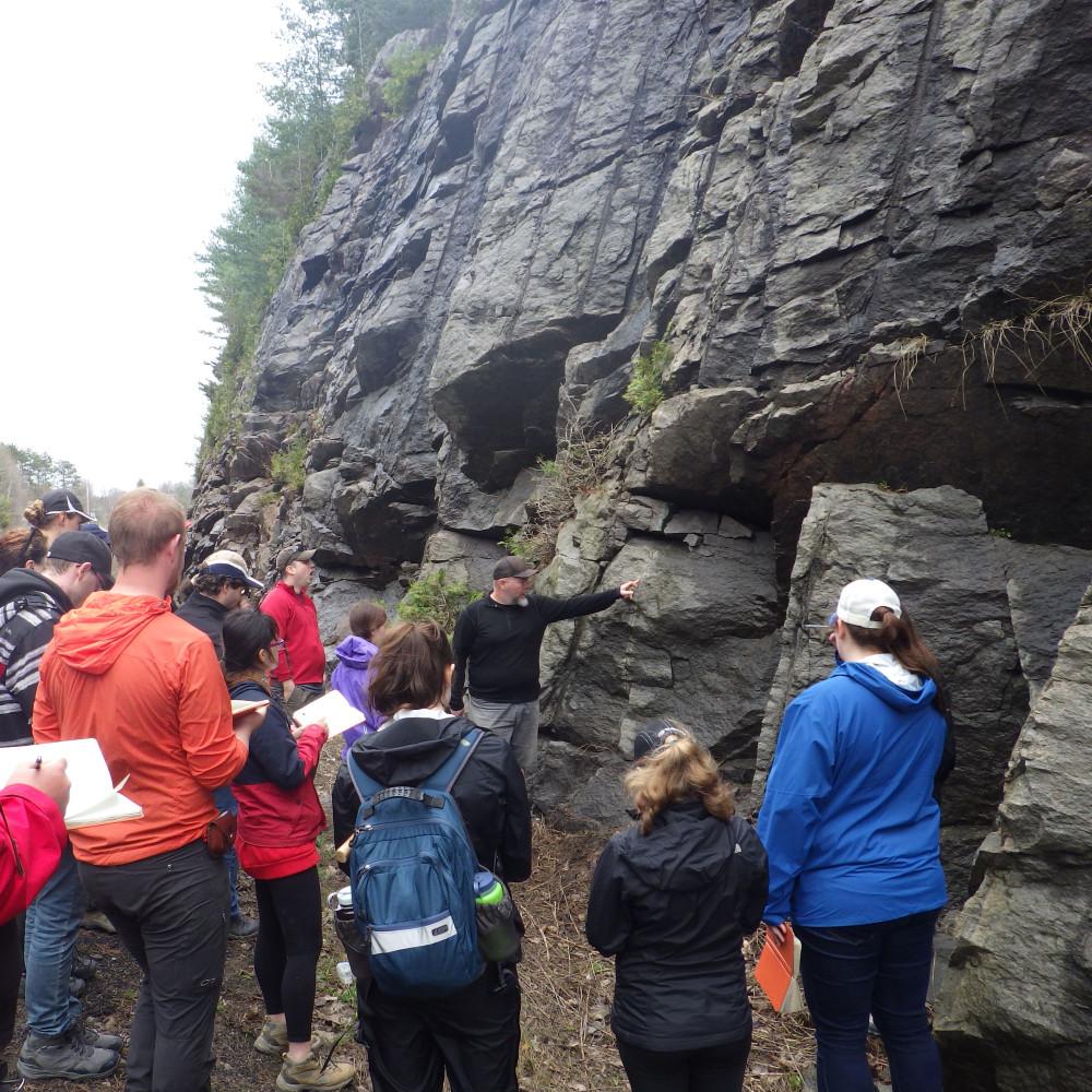 Un groupe d'étudiants se rassemble autour d'un professeur devant une paroi rocheuse au bord d'une route. Le professeur signale une fissure dans la paroi rocheuse. Certains élèves prennent des notes dans leur carnet de notes.