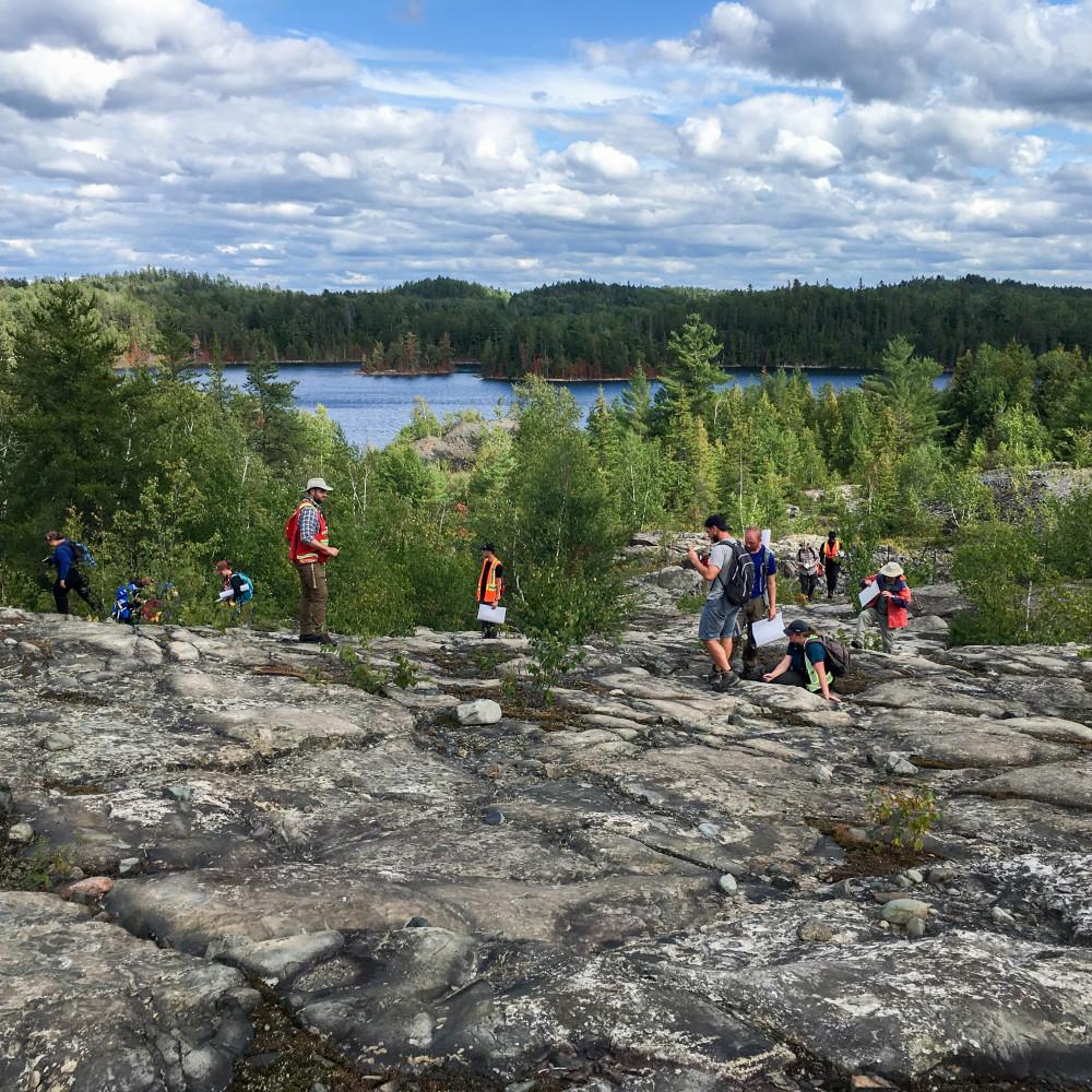 Un groupe d'étudiants explore dans la nature sur une surface rocheuse exposée près d'un lac.
