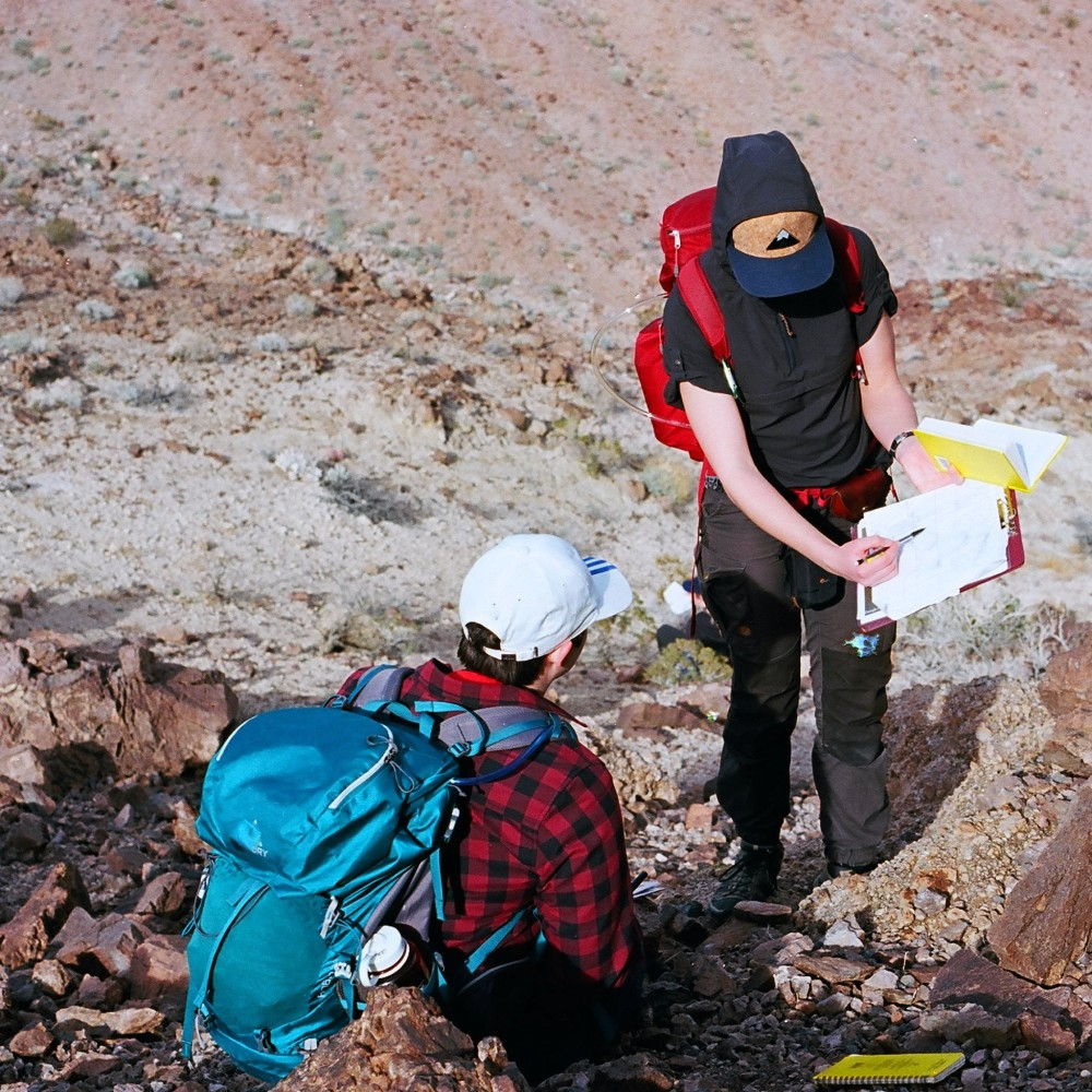 Deux étudiants de Death Valley, passant en revue les notes de terrain. Les deux portent des sacs à dos. Un élève est assis tandis que l'autre pointe vers un graphique dans un presse-papiers qu'il tient. Le terrain est très rocheux avec quelques arbustes.