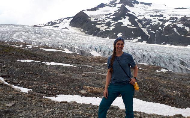 L'étudiante se tient devant une montagne enneigée